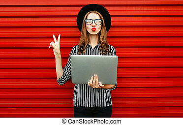 Caucasian young woman with laptop on red wall background