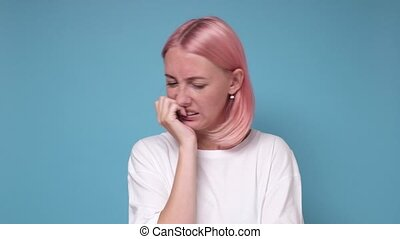 Caucasian young woman with pink dyed hair bites nails ...