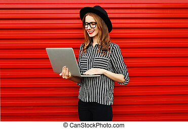 Caucasian young woman working with laptop on red wall background