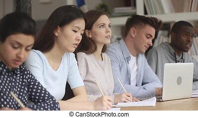 caucasien, notes, conférence, écouter, international, étudiant, écrire, concentré, camarades classe
