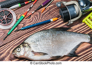 caught fish and fishing tackle on a wooden table