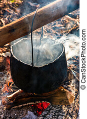 cauldron in steam and smoke on open fire. outdoor cooking...