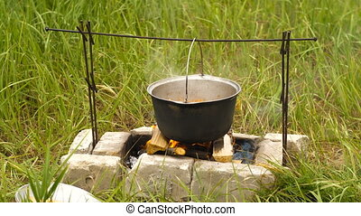 Cauldron on a fire - Cooking with touristic cauldron on...