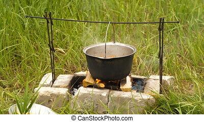 Cauldron on a fire - Cooking with touristic cauldron on...