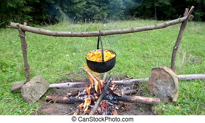 Cauldron with boiling mushrooms on the fire
