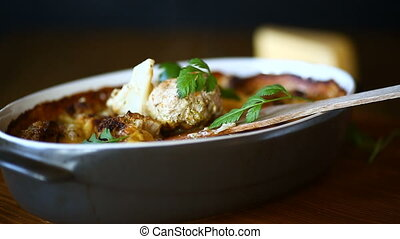 Cauliflower baked with meatballs in cheese sauce, in ceramic...
