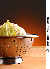 Cauliflower in Colander on rustic wood table