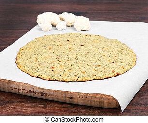 Plain cauliflower pizza crust on a piece of parchment paper on a cutting board. Selective focus on front edge of crust.