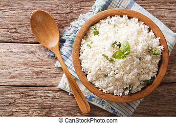 Cauliflower rice with basil in a bowl close-up. Horizontal...