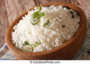 Cauliflower rice with basil in a bowl close-up. horizontal -...
