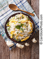Cauliflower rice with scrambled eggs and herbs. vertical top view