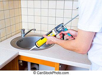 Caulking gun putting silicone sealant to installing a...