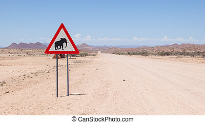 Caution: Elephants! Road sign standing beside road
