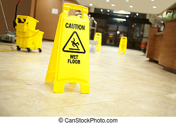 """Lobby floor with mop bucket and """"caution wet floor"""" signs, selective focus on nearest sign"""
