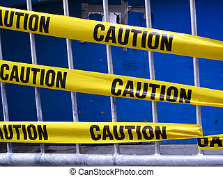 Caution Tape - Yellow caution tape on a metal barrier