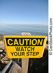 Caution Watch Your Step sign by the ocean - A Watch Your...