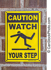 Caution Watch Your Step sign on a brick wall