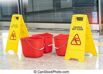"""""""Caution wet floor"""" sign with mop bucket"""