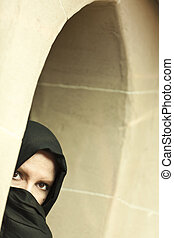 Cautious Islamic Woman in Window Pane Wearing Burqa or Niqab...
