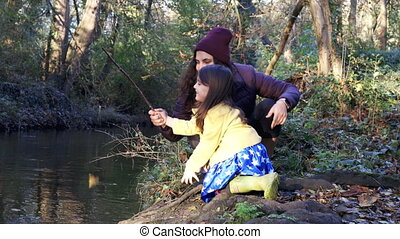 Cautious mother holding her little daughter who picks the river with a stick in forest. Mother and daughter fun day in nature. Adventurous day in forest