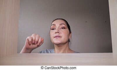 Cautious woman comes to take hidden dollar bills from drawer wooden shelf far corner, smiles in walk-in closet at home close view from rack