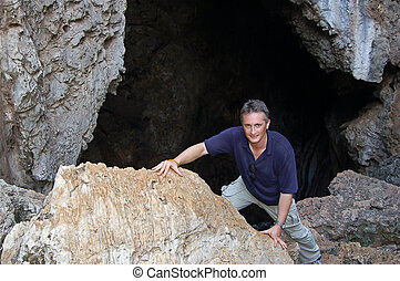 Cave mouth - Man emerging from a steep cave mouth