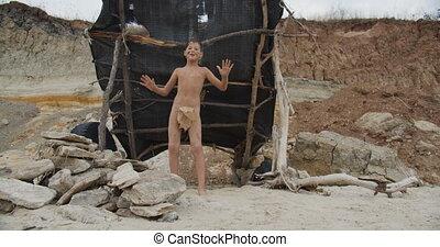 Caveman, manly boy dancing . Funny young primitive boy...