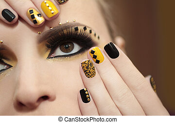 Caviar manicure in yellow and black nail Polish on the girl with false eyelashes and rhinestones of different shapes.