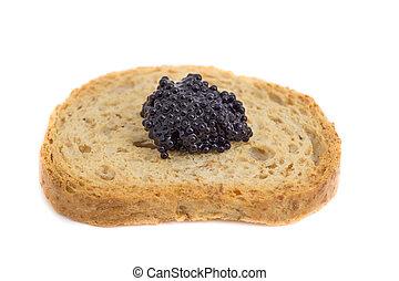 Caviar over piece of toast - Closeup view of caviar over...