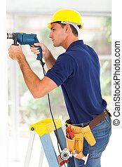 cctv camera installer drilling on the wall