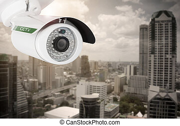 CCTV, security camera on building city background.