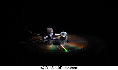 cd compact disk and white headphones on a dark background. concept: listen to music