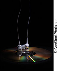 cd compact disk and white headphones on a dark background. concept: relax music
