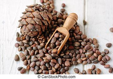 Cedar nuts in wooden scoop over heap of cedar nuts.