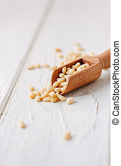 Cedar or pine nuts in a wooden scoop over white table.