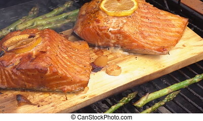 cedar plank salmon with lemon cooking on grill - cedar plank...