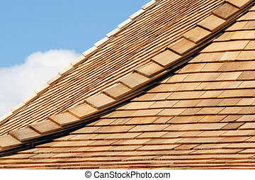 Roof of new cedar shingles - blue sky and clouds in background