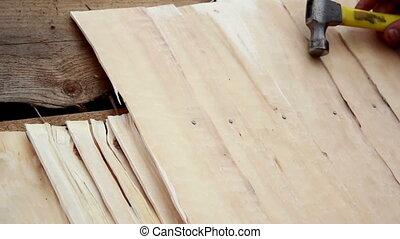 cedar wooden shingle shake roofer wearing bandaid in his left pointer finger
