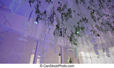 Ceiling decorated with white flower in interior of wedding banquet hall.