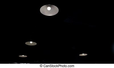 Ceiling with built in halogen lamps, switching on slowly in darkness.