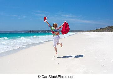 Celebrate Christmas in Australia - female jumping for joy on...