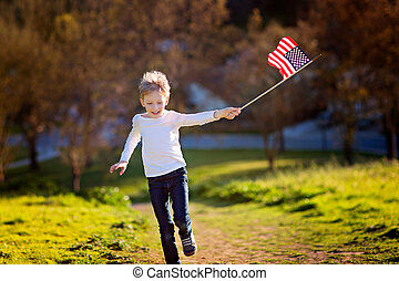 celebrating 4th of july - cheerful active little boy running...
