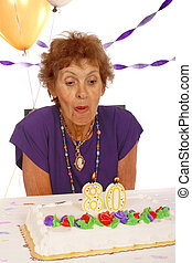 Celebrating 80 Years - A woman preparing to blow out the...