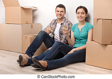 Celebrating a new dwelling. Beautiful young loving couple sitting on the floor and holding glasses with wine while cardboard boxes laying around them