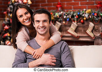 Celebrating Christmas together. Beautiful young loving couple bonding to each other and smiling while sitting on the couch with Christmas Tree in the background