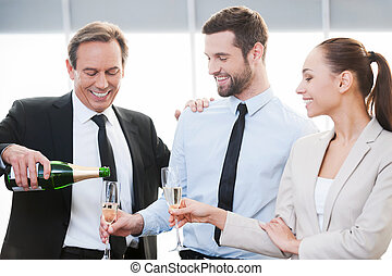 Celebrating good contract. Happy mature businessman pouring champagne while man and woman in formalwear standing close to him and holding champagne flutes