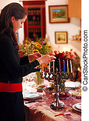 Celebrating Hanukkah - A woman prays before lighting candles...