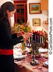 Celebrating Hanukkah - A woman prays before lighting candles...