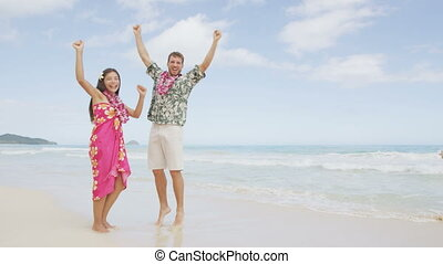 Celebrating happy winning couple Hawaii beach - Celebrating ...