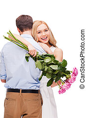 Celebrating love. Beautiful young loving couple hugging while woman holding bouquet of pink roses and smiling and both standing isolated on white background